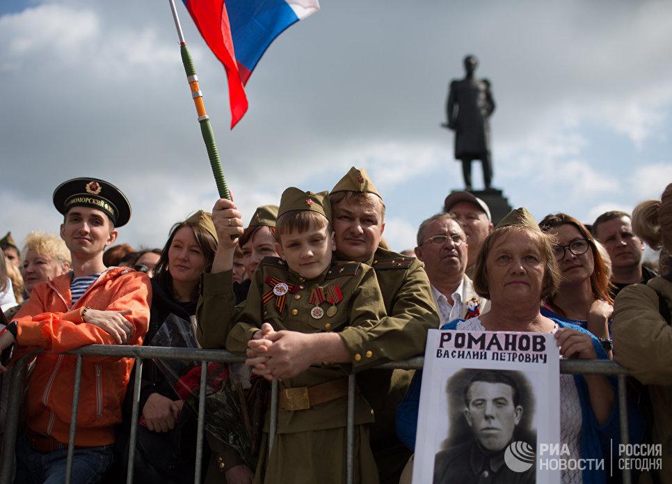 Жители Севастополя во время военного парада в Севастополе, посвященном 72-й годовщине Победы в Великой Отечественной войне и 73-й годовщине освобождения города от немецко-фашистских захватчиков